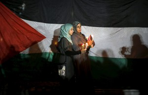 Women hold candles as they stand in front of a Palestinian flag during a rally to pay tribute to Palestinians who organizers said were killed recently by Israeli troops, on Christmas day in Gaza City