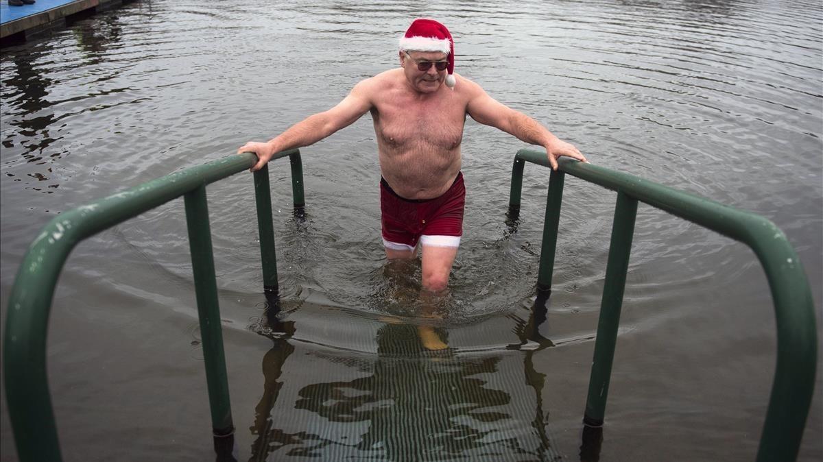Un hombre sale de un baño en las aguas del Lago Serpentine en Hyde Park durante el baño anual de Navidad en el centro de Londres.