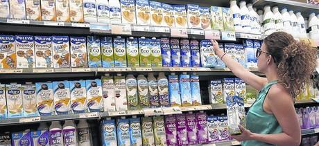 Una clienta elige leche entre la gran variedad de oferta del supermercado.
