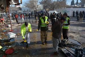 Crime scene investigators collect evidence from the site of a suicide bomb attack close to a polio eradication centre in Quetta