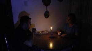 Una pareja toma un café en una establecimiento público a la luz de las velas.