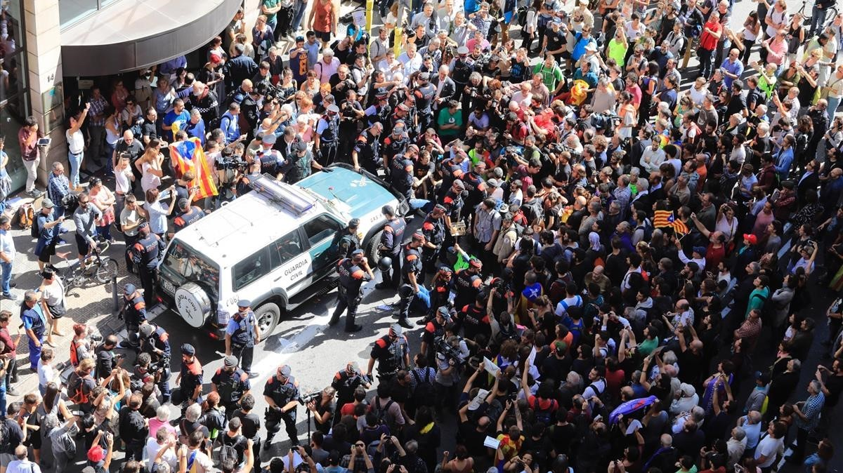 Decenas de personas intentan impedir que salga el coche de la Guardia Civil tras el registro al Departament dAfers Exteriors de la Generalitat.
