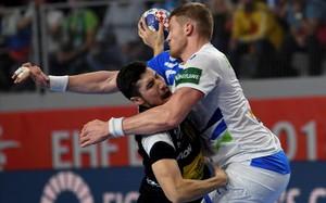 El lateral español Alex Dujshebaev choca contra el pivote esloveno Blagotinsek