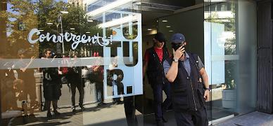 Agentes de la Guardia Civil salen de la sede de CDC tras el registro
