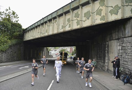 Spectators watch as a torchbearer runs in the Olympic Torch Relay in Plymouth, south west England May 20, 2012. Some 8,000 runners are participating in the Olympic Torch Relay which will cover over 8,000 miles throughout Britain, Northern Ireland and Ireland over the next ten weeks before the London 2012 Olympics. REUTERS/Toby Melville (BRITAIN - Tags: SPORT OLYMPICS)