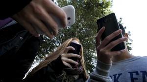 Adolescentes con sus teléfonos móviles.