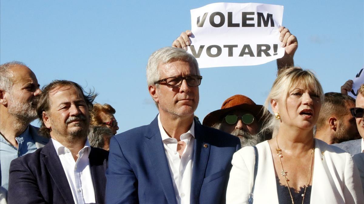 El alcalde de Tarragona, Josep Felix Ballesteros, con los regidores Pau Perez y Elvira Ferrando ante una pancarta de Volem votar.