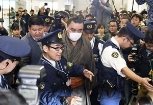 Mongolian-born grand sumo champion Yokozuna Harumafuji is escorted by police officers upon his arrival at Haneda airport in Tokyo