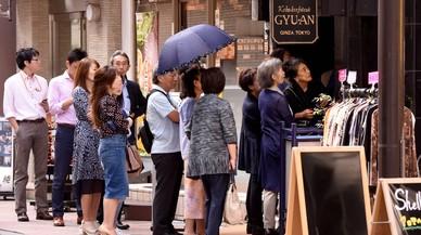Un grupo de japoneses espera para entrar a un restaurante en Tokyo.