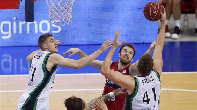 Tomasz Gielo iGarrett Stultz, del Joventut, lluitant per un rebot ambMartynas Gecevicius, del Tecnyconta Zaragoza.