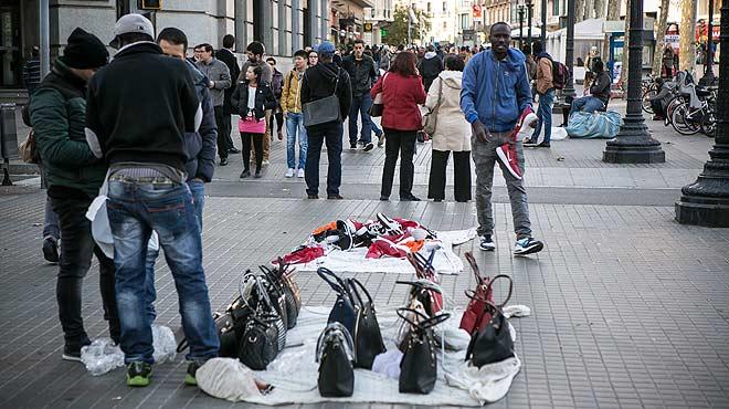Manteros en el centro de Barcelona se dispersan ante la presencia de agentes de la Guardia Urbana.