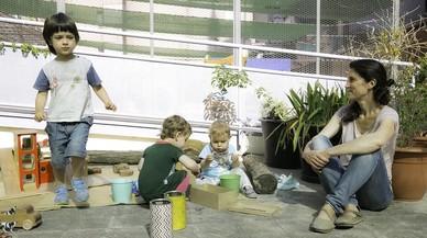Tres niños juegan en el área exterior del Espacio Familiar del Raval, ante la mirada de una madre, este martes.