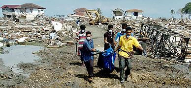 Voluntarios trasladan cad�veres de Ule Lhee, en Banda Aceh, en enero del 2005.