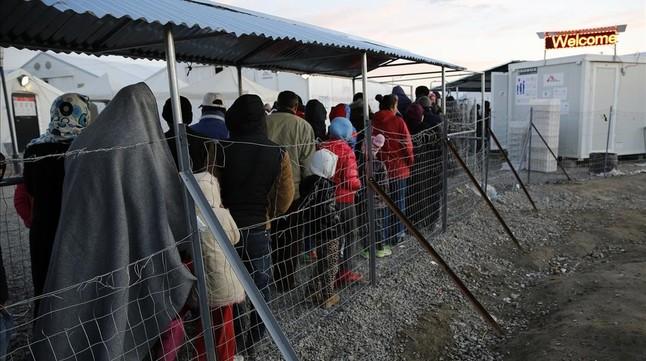 Refugiados y migrantes hacen cola durante la distribución de comida en un campamento cercano a Idomeni, en la frontera de Grecia con Macedonia, este jueves.