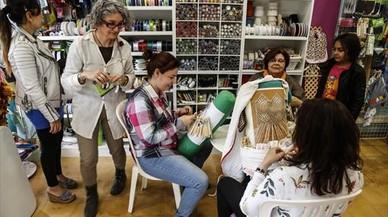 Gemma Vidal (segunda por la izquierda) departe con clientas en la mercería Fòrum de Labors.