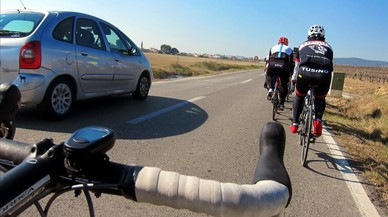 Dos ciclistas circulan por una carretera catalana.