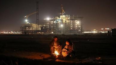Migrants, a la vora del foc, en un magatzem duaner abandonat a Belgrad.