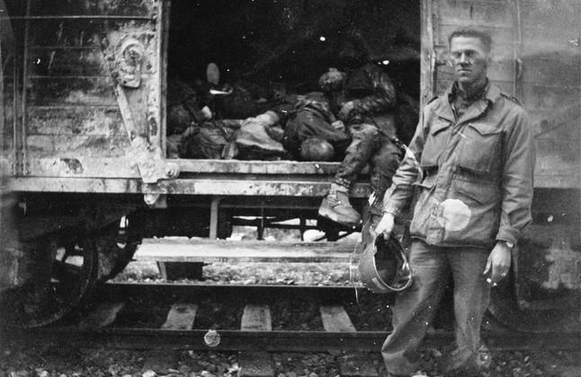 Un soldado estadounidense, ante un tren cargado de reclusos muertos poco después de la liberación de Dachau. Habían  salido de Buchenwald unas tres semanas antes.