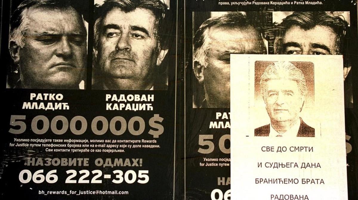 Carteles con la recompensa ofrecida por Mladic y Karadzic, con otro en serbio con proclamas a su favor, en Foca (este de Bosnia), el 5 de marzo del 2002.