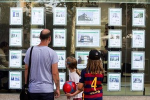 Un hombre y dos niñas observan las ofertas de viviendas en una agencia inmobiliaria del paseo de Maragall de Barcelona.