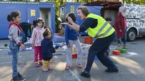 Una voluntària juga amb uns nens en un camp de refugiats a Salzburg.