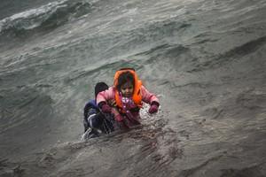 Un hombre ayuda a un niño cuyo barco ha naufragado este domingo en el Egeo.
