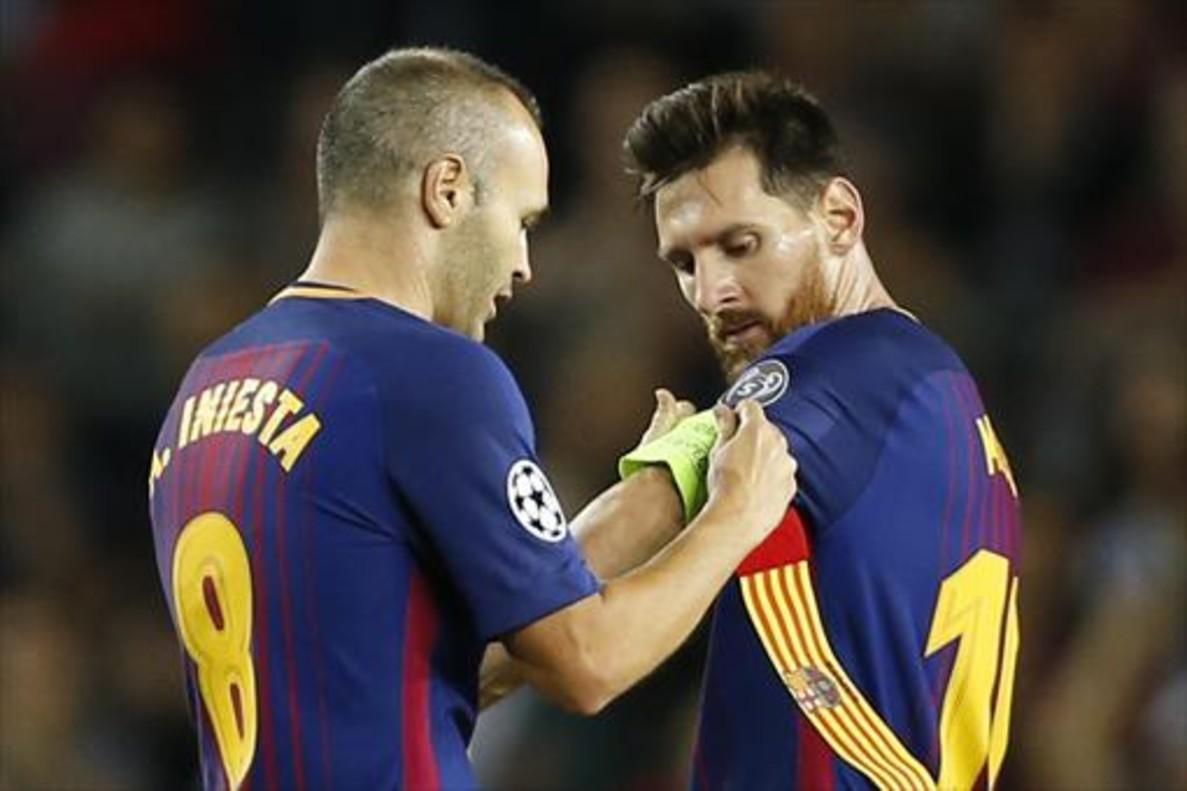 Iniesta pone el brazal de capitán a Messi.