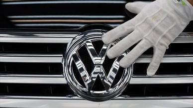 Un empleado coloca el logotipo de Volkswagen a un vehículo.