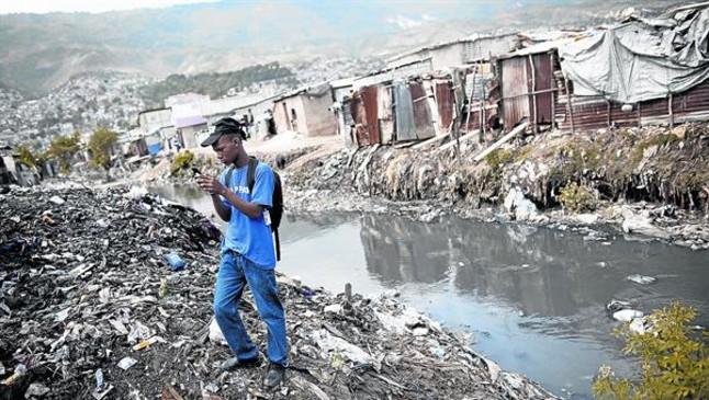 <b>ETIQUETADO.</b> <br/>Un hombre fotografía un vertedero en <br/>Puerto Príncipe.