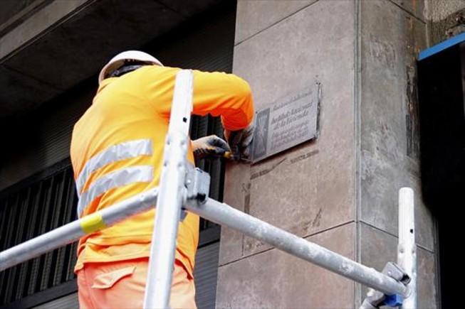Un operario municipal retira una placa franquista en Barcelona, ayer.