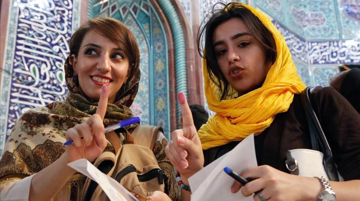 Mujeres muestran sus huellas en Teherán tras emitir su voto durante las elecciones presidenciales en Irán.