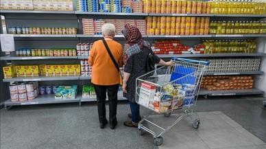 Dos mujeres observan una estanter�a en un supermercado de C�ritas.