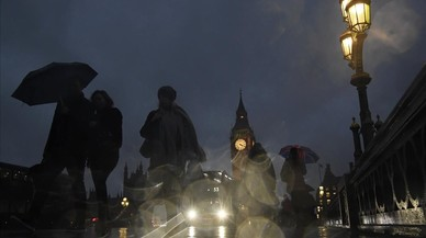 Gente caminando por el puente de Westminster bajo la lluvia a consecuencia de una huelga convocada por los sindicatos del metro de Londres.