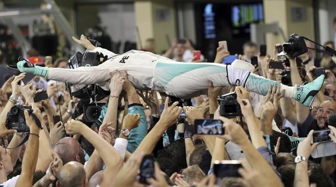 Nico Rosberg, manteado por su equipo de mecánicos.