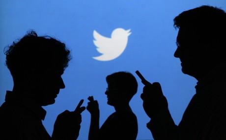 Personas utilizando su tel�fono ante una imagen del logo de Twitter.