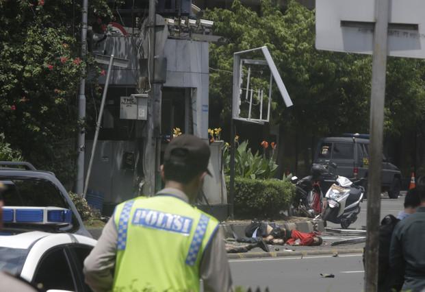 Dos víctimas del atentado yacen en el suelo, en una zona acordonada por la policía.