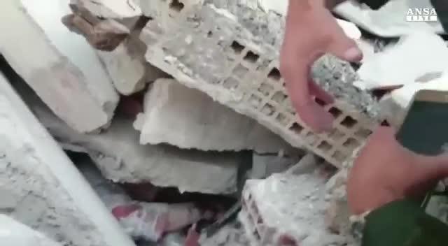 Un socorrista intenta calmar a una persona atrapada entre los escombros.