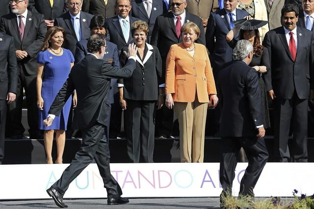 Rajoy y Merkel conversan brevemente tras su cruce de acusaciones