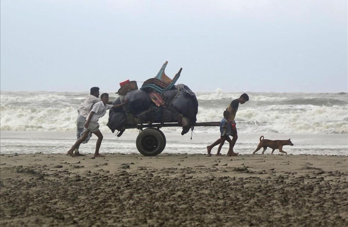 Una familia empujaun carro con sus pertenencias de regreso a sucasa después de pasar una noche en un refugio en Cox s Bazar, Bangladesh, tras el paso de una tormenta tropical.