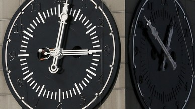 Worker adjusts hands on clock face of city administration building during clock's restoration in Krasnoyarsk