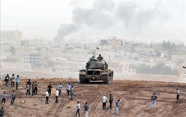 Kurdos de Turquía observan junto a un tanque las columnas de humo que salen de la ciudad siria de Kobani.