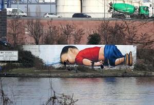 Un enorme grafiti de Aylan ocupa un muro junto al río Main en Fráncfort.