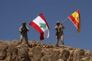 Dos soldados ondean las banderas libanesa y española tras recuperar parte de la región de Ras Baalbek.