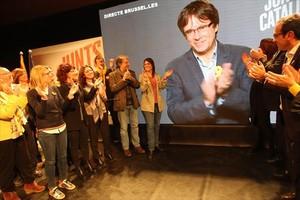El escenario del mitin de JxCat, con Puigdemont en la pantalla y su esposa aplaudiendo (tercera por la izqda.).