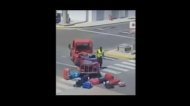 Un operari de l'aeroport d'Eivissa llança a l'aire les maletes dels passatgers