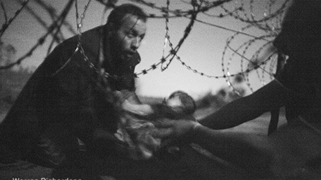 Un refugiado con su beb� en la valla de la frontera de Hungr�a, la foto de Warren Richardson ganadora del World Press Photo 2016.