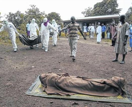 Unos enfermeros trasladan a una víctima del ébola, en Monrovia (Liberia).