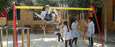 Unas ni�as juegan en los columpios de la escuela de Abu Hindi.