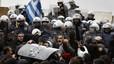 Manifestantes se hacen con un escudo policial en las protestas ante el Parlamento griego, este martes, en Atenas.