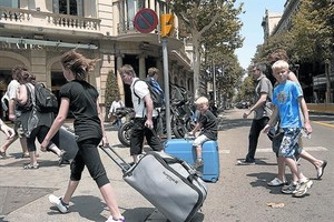 Turistas con maletas rumbo a su alojamiento recorren el paseo de Gràcia.